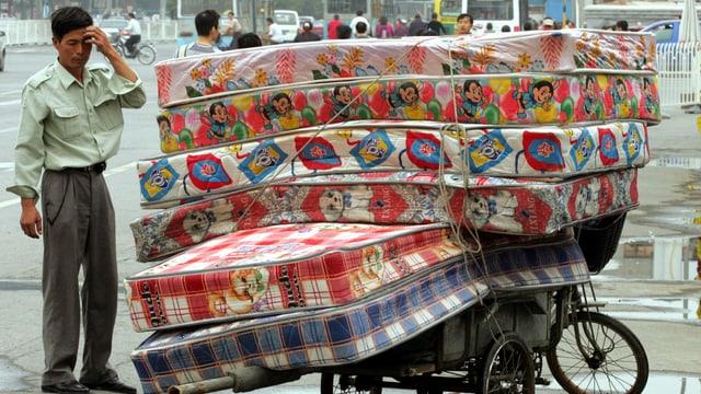 Ein Mann bestaunt aufgestapelte Matratzen.