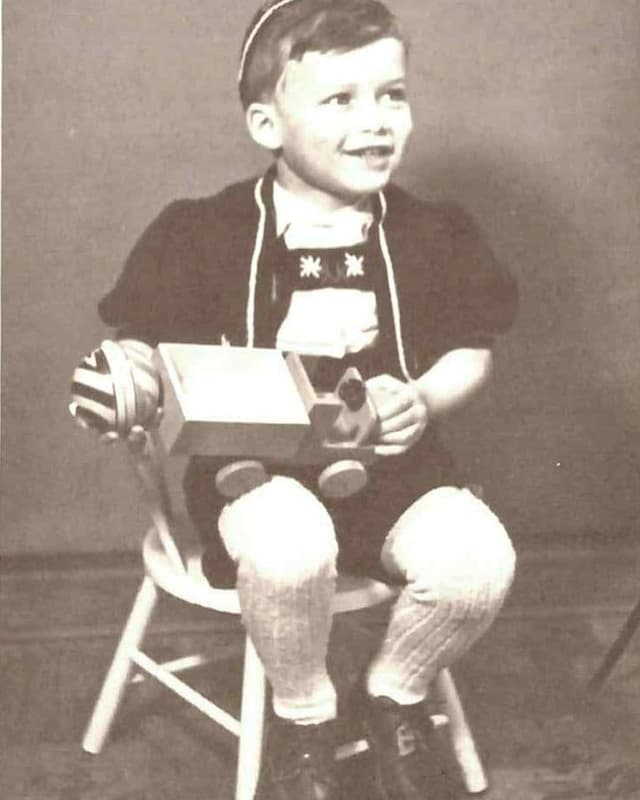 Kleiner Junge mit Holzauto auf Stuhl.