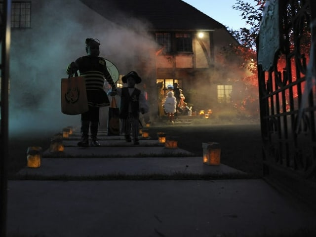Kinder gehen Gehweg entlang der mit Laternen geschmückt wurde.