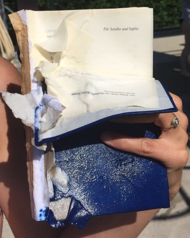 Annette König hält nach Tauchgang mit Buch, das Buch «Mein Vater war ein Mann an Land und im Wasser ein Walfisch» von Michelle Steinbeck in der Hand. Es ist leicht zerstört.