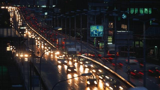 Stau auf der Zürcher Hardbrücke beim Eindunkeln: die Autos bilden eine Lichterschlange.