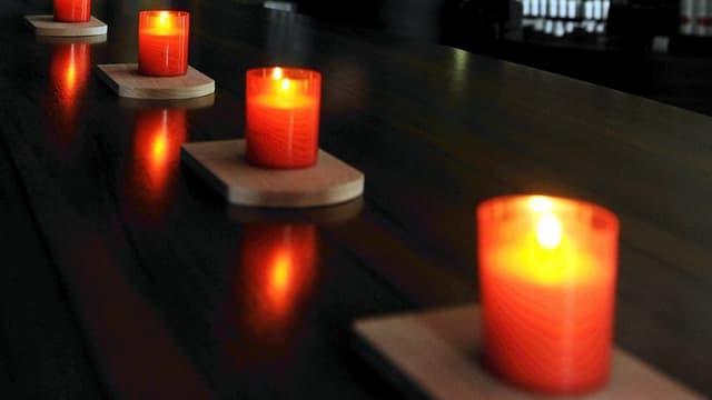 Vier Kerzen auf einer schwarzen Theke.