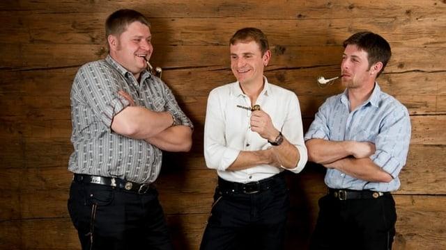 3 Männer lehnen lachend an eine Holzwand, jeder eine Tabakpfeife in der Hand oder im Mund.