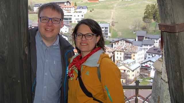 Ein junger Mann und eine junge Frau auf einem Kirchturm mit Blick aufs Dorf.