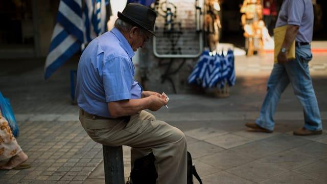 Ein Mann sitzt auf einem Pfosten und zählt sein Geld