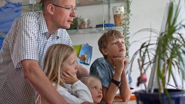 Vater sitzt mit drei Kindern vor Computer. Symbolbild für den Erfolg von Familienunternehmen.