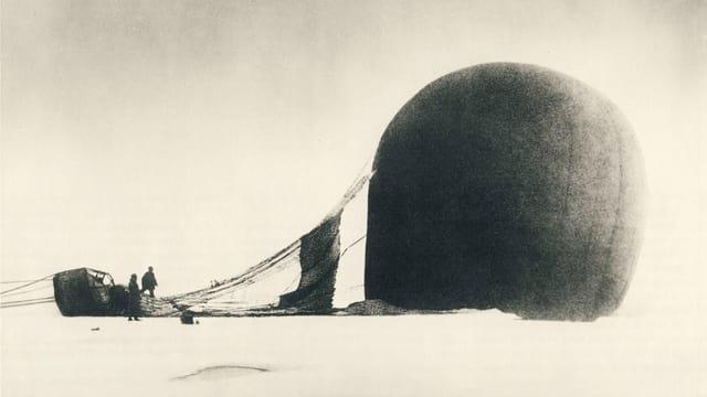 Alte Fotografioe eines Ballons mit Gondel, der auf einer Eisfläche am Boden liegt.