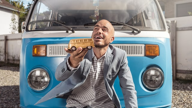 Sänger Dodo posiert vor seinem blauen VW-Hippie-Bus und hält dabei einen kleinen Goldbus aus Karton in den Händen.
