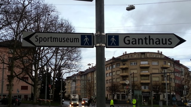 Zwei Wegweiser, einer weist in Richtung Sportmuseum