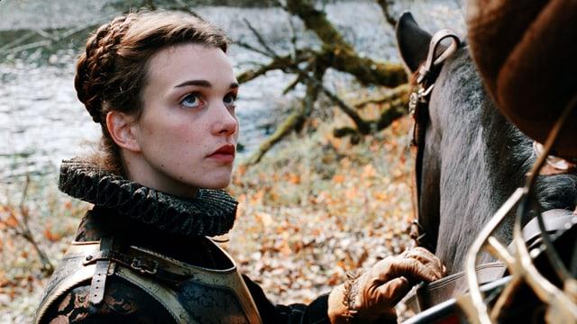 Nahaufnahme einer Frau in Rüstung. Sie steht neben einem Pferd und schaut zum Reiter hoch, Dieser ist nicht im Bild.