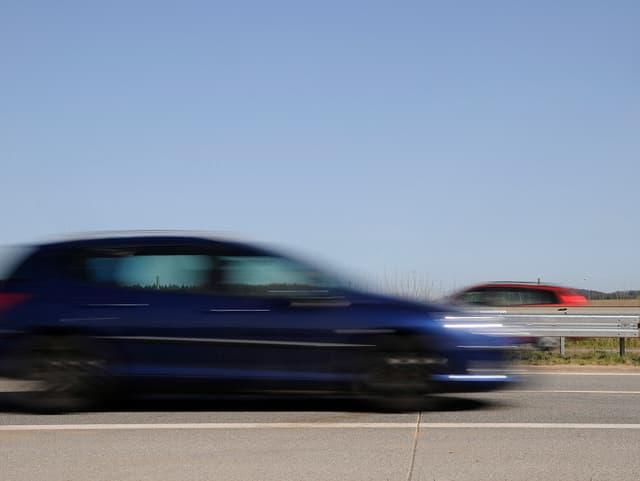 Verschwommenes Auto auf einer Autobahn, von der Seite fotografiert