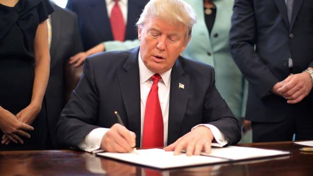 Trump unterschreibt ein Dekret.