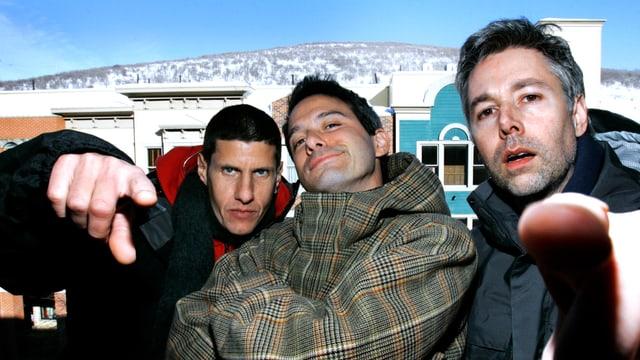 Drei junge Männer, der in der Mitte hat die Arme verschränkt, die beiden aussen zeigen mit dem Finger in die Kamera.
