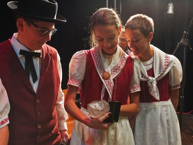 Mädchen und Junge in Tracht begutachten Pokal mit Bergkristall.