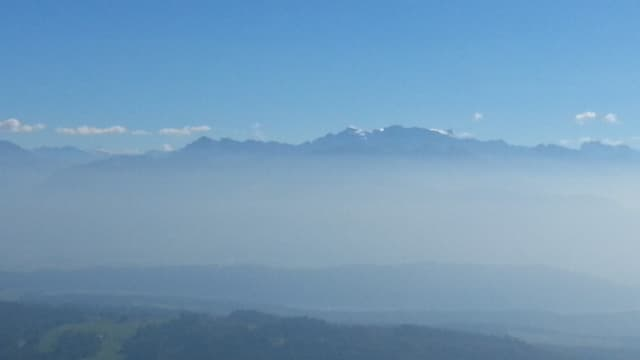 Bild vom Bachtel Richtung Glarner Alpen. Über den Bergen hat es ganz vereinzelt Quellwolken, und über dem Mittelland liegt Dunst.