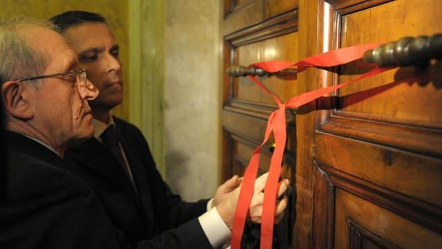 Angestellte des Vatikans verschliessen eine Tür symbolisch mit einem roten Band.