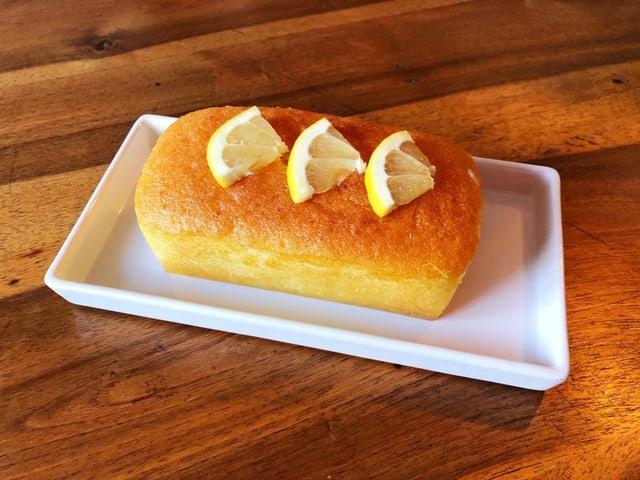 Ein kleiner Zitronenkuchen auf einem Holztisch.