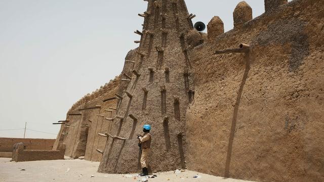 UNO-Blauhelm steht vor einem Sandsteingebäude.
