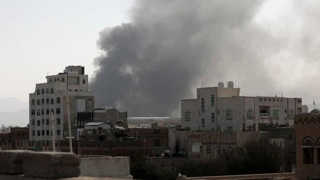 Hinter Gebäuden der Stadt steigt Rauch auf.