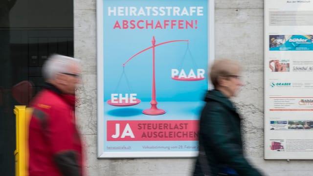 Ein Mann und eine Frau gehen an einem Plakat vorbei, das für ein Ja zur Initiative gegen die Heiratsstrafe wirbt.