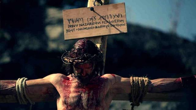 Jesus, der mit Seilen ans Kreuz gebunden ist, lässt den Kopf hängen.