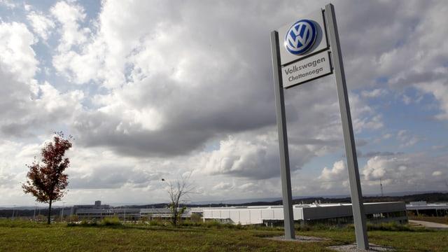 Das Logo des Autoherstellers VW, im Hintergrund die Fabrik