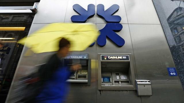 Eine Frau mit Regenschirm geht an einem Bankomat der Royal Bank of Scotland vorbei. Die Bank muss eine weitere Millionen-Busse im Libor-Skandal zahlen. (reuters)