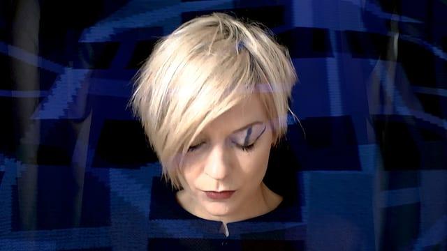 Eine blonde Frau mit kurzem Haar, deren blauschwarzes Kleid ihr über den Kopf zu wachsen scheint.