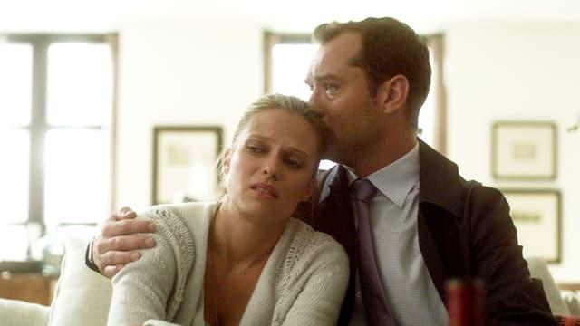 Eine Frau lehnt sich an einen Mann, er küsst ihren Kopf.