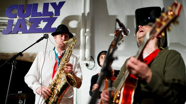 Drei Jazz-Musiker auf der Bühne in einem Keller.