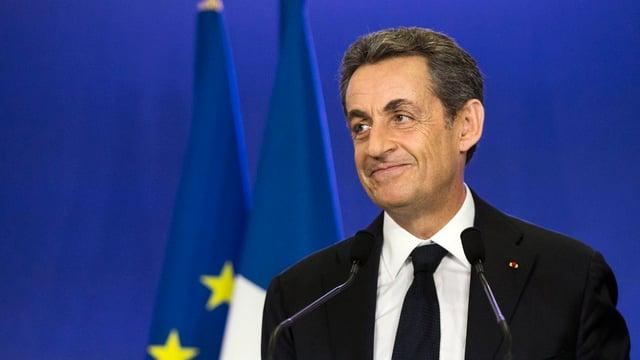 Sarkozy lächelt verschmitzt. Im Hintergrund die französische und europäische Flaggen.