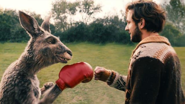 Filmszene: Ein Känguru mit Boxhandschuh und ein Mann in Strickjacke schlagen die Fäuste aneinande rund grinsen.
