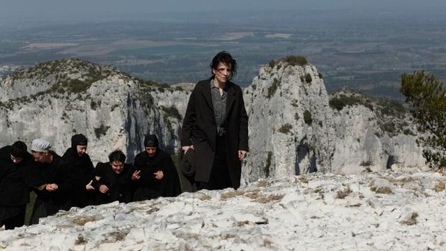 Juliette Binonche wandert auf einen Berg, gefolgt von Mitinsassinnen.