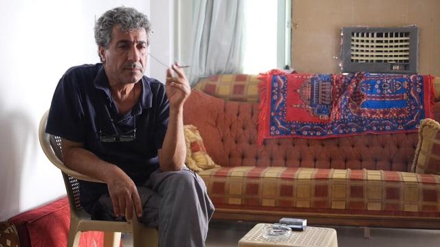 Taha Khalil sitzt rauchend an einem Tisch