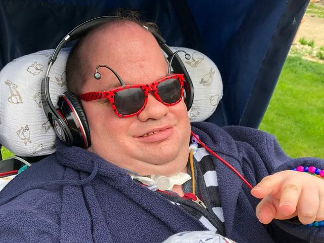 Darcy mit Kopfhörer und Sonnenbrille.