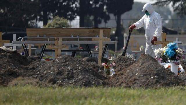Mann in Schutzanzug auf Friedhof
