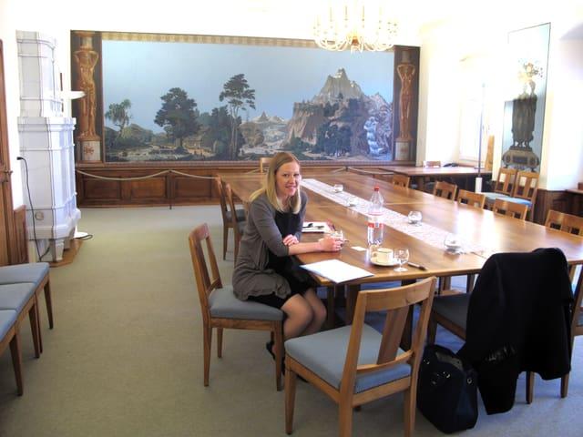 Frau sitzt an einem Holztisch in einem grossen Saal.