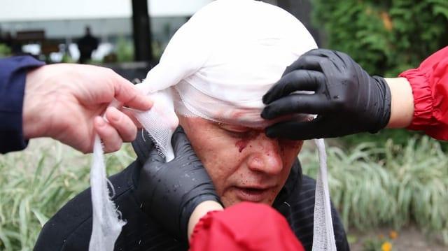 Ein verletzter Demonstrant wird notdürftig verarztet.