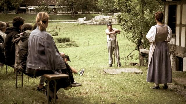 Freilufttheater: Ein Mann spricht mit einer Frau, beobachtet von Zuschauern auf einer Bank.
