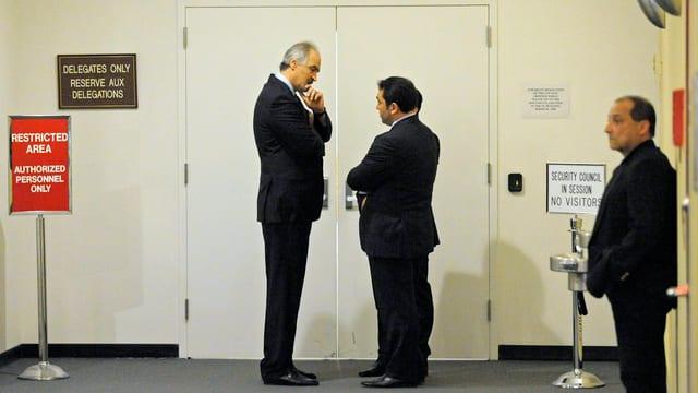 Jafaari mit zwei Diplomaten vor geschlossener Tür