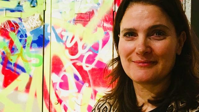 Frau mit dunklen Haaren vor farbigem Hintergrund.