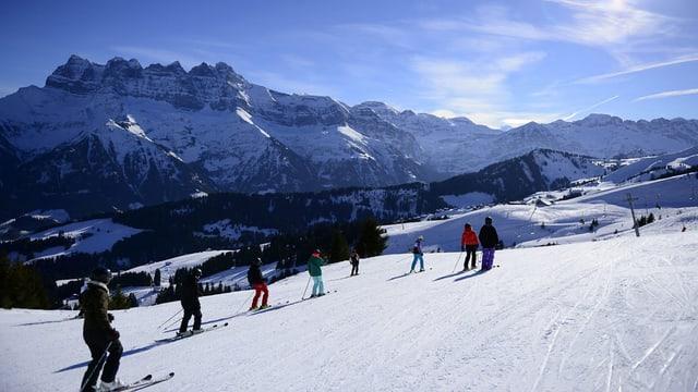 Skifahrer auf der Piste, bei herrlichem Wetter und Berpanorama