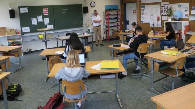 Schülerinnen und Schüler sitzen an Einzelpulten. Vorne steht Lehrer Franz Gehrig.