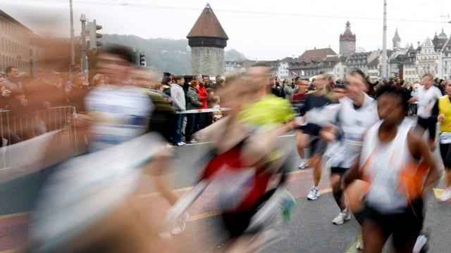 Marathonläufer rennen über die Luzerner Seebrücke.