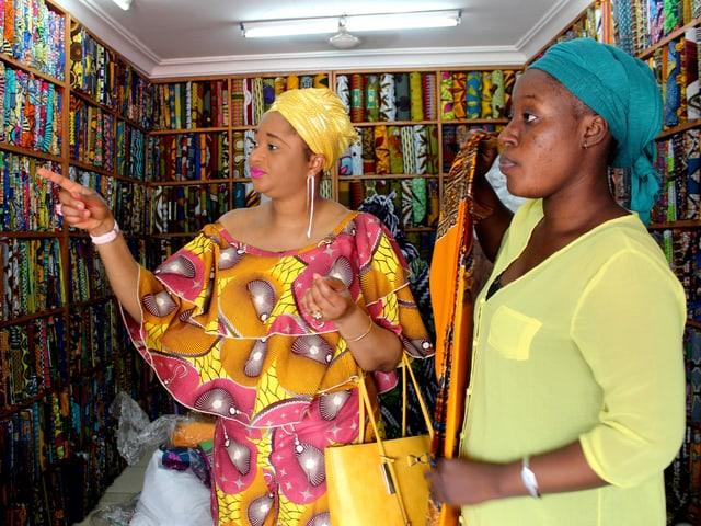 Zwei Frauen in bunter Kleidung vor Regalen mit bunten Stoffen