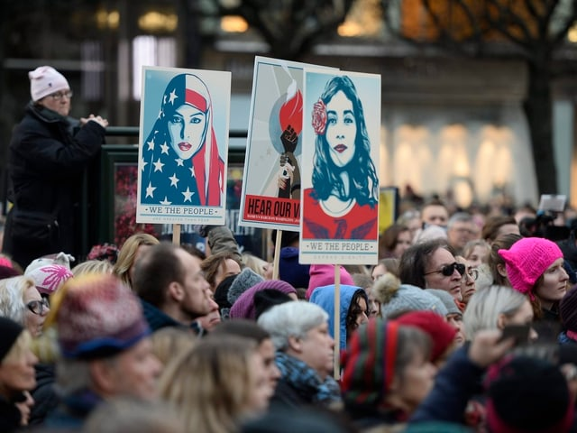 Demonstranten, Plakate von Frauen.