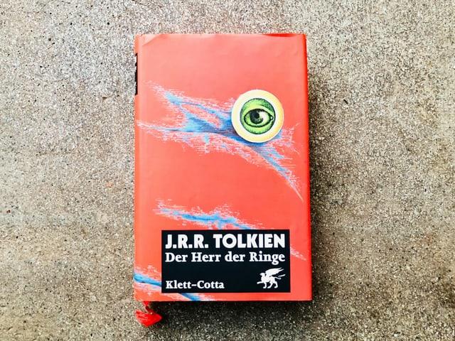 Der Roman «Der Herr der Ringe» von J.R.R. Tolkien liegt auf einem Zementboden
