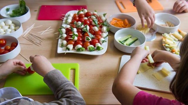 KInderhände schneiden Gemüse.