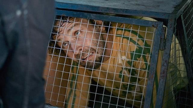 Ein Mann in einem Hundekäfig