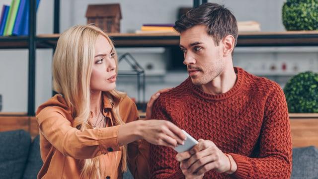 Eine Frau nimmt dem Mann sein Handy aus der Hand.